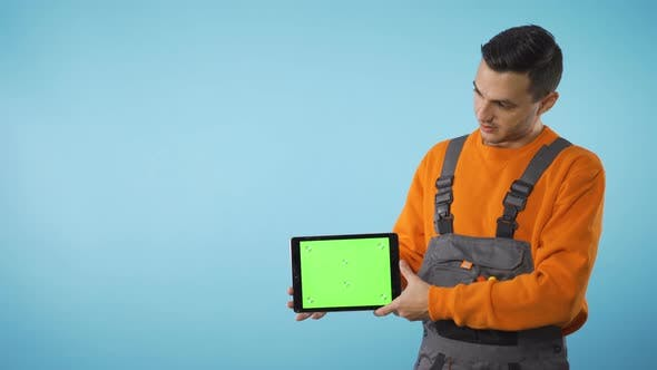 Green Screen Tablet in Mans Hand with Copy Space Isolated on Blue Background