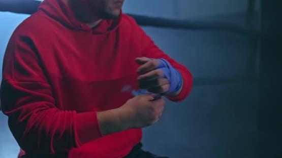 Nahaufnahme ein männlicher Athlet umschließt seine Hände und Finger mit Bandagen zum Schutz während des Trainings