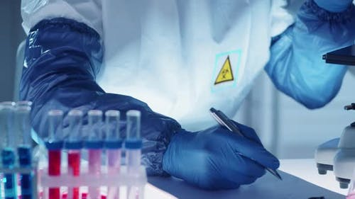 Virology Scientist in Protective Uniform Using Microscope and Taking Notes
