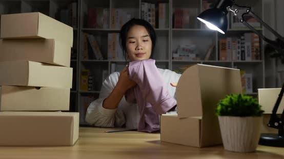 Frau packt ein Produkt in die Box