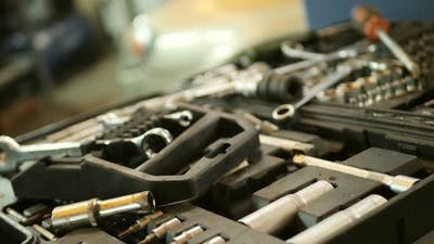 Auto Mechanic Takes a Tool in Mechanics Garage