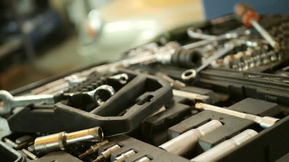 Automechaniker nimmt ein Werkzeug in der Mechaniker-Werkstatt