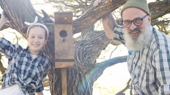 Thumbnail for Aged Man and His Granddaughter near Birdhouse