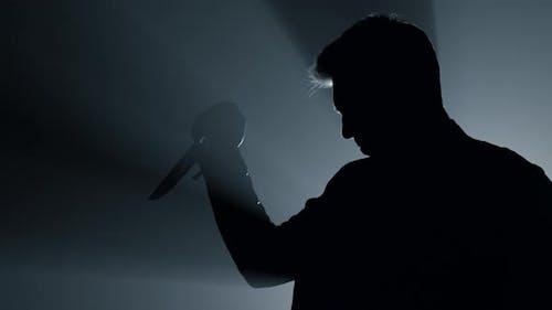 Silhouette Grausamer Killer Stechen mit Messer drinnen
