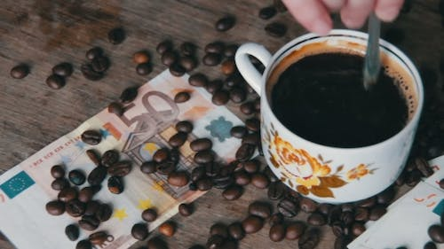 Coffee Beans, Coffee Cup And Euro On a Wooden Table