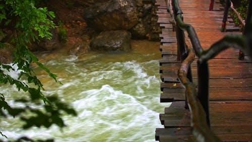 Wooden Bridge Hanging Over Rough River