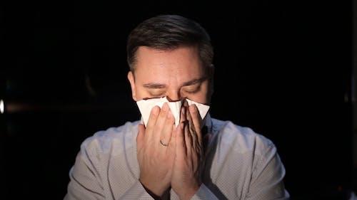 Man Sneezes Into A Tissue