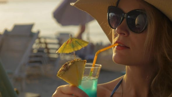 Thumbnail for Woman In Hat And Sunglasses Drinking Cocktail