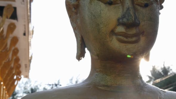 Thumbnail for Face Of Golden Buddha Against Sunset In Temple