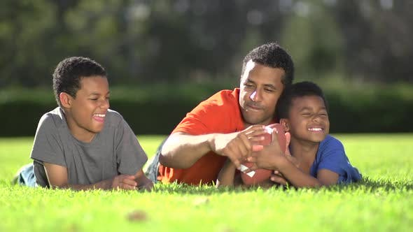 Thumbnail for Group portrait of a father and his sons with a football