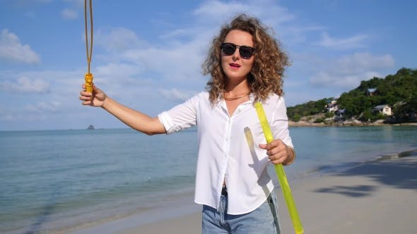 Thumbnail for Girl With Curly Hair Blowing Bubble On Beach In Summer