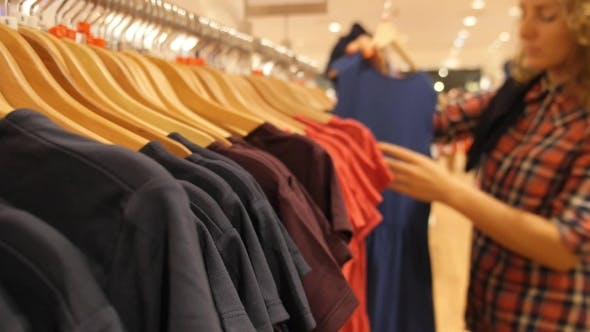 Thumbnail for Young Woman Choosing Clothes In Shopping Mall