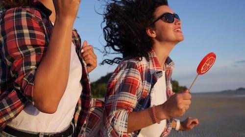 Happy Funky Girls Running On Beach At Sunset