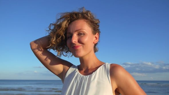 Thumbnail for Beautiful Girl With Curly Hair Flirting At Beach