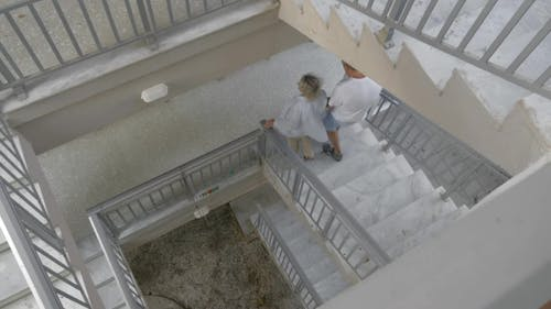 Couple Walking Down The Spiral Stairs