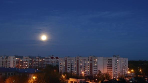 Thumbnail for Time Lapse of big Full Moon Moving over residential apartment building in big city