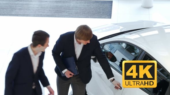 Thumbnail for Salesman Explains To Customer Car Specifications