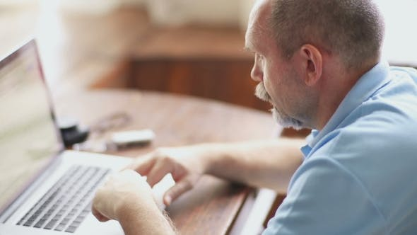 Thumbnail for Senior Man Works With Laptop