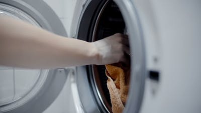 Woman Loading The Laundry In The Washing Machine