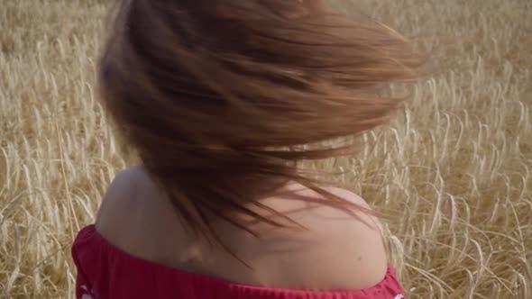Thumbnail for Rückansicht der attraktiven Frau scharf Drehen und Blick auf die Kamera auf dem Weizenfeld, Haare