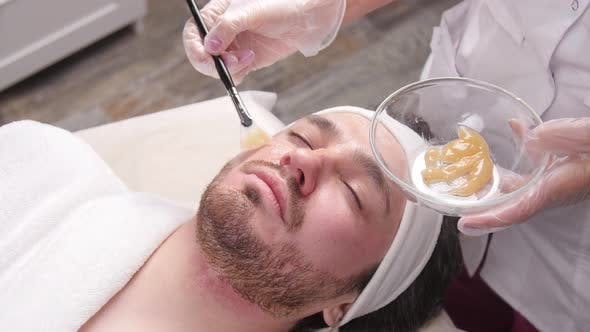 Young Man with Clay Facial Mask in Beauty Spa