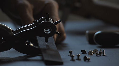 Handicraftsman Piercing Holes In Leather Material