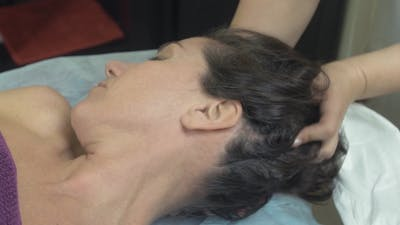 Masseuse Make Healing Massage Of Head To Young Woman