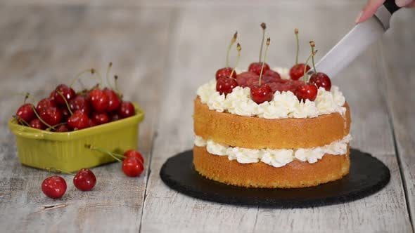 Cover Image for Woman Is Cutting The Naked Cherry Cake With Vanilla Cream.