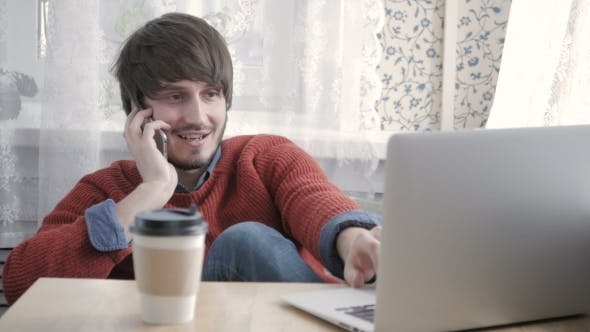 Thumbnail for Happy Young Man Freelancer Working With Modern Laptop And Phone In Cafe Taking Cup Of Coffee