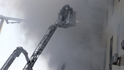 Fully Equipped Firefighter on a Ladder