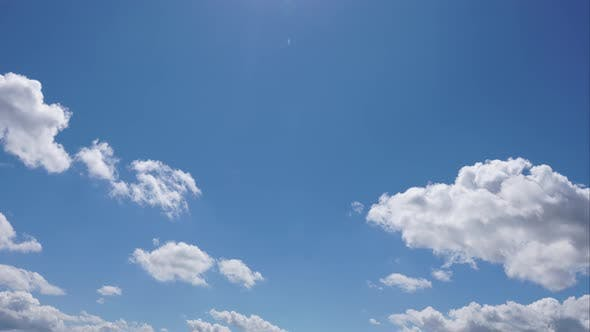 Time lapse of white cumulus clouds flying in the blue sky.