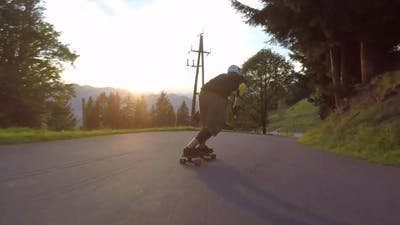 A skateboarder downhill skateboarding racing on a mountain road.