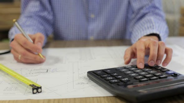 Engineer Designer Makes Calculations on a Calculator