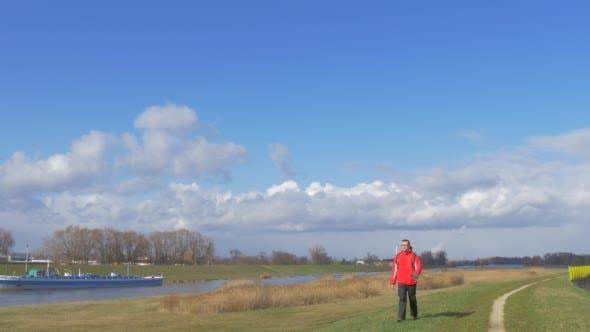 Backpacker is Walking Along a River Toward Camera