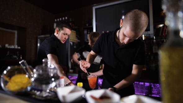 Thumbnail for Several Bartenders In Stylish Black Shirts, Work In Intensive Mode.