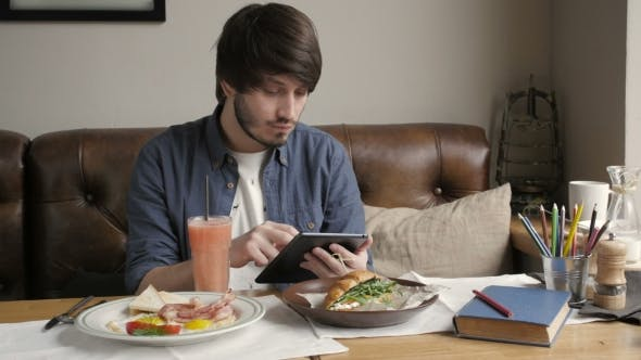 Thumbnail for Hipster Man Using Digital Tablet  Eating Healthy Breakfast