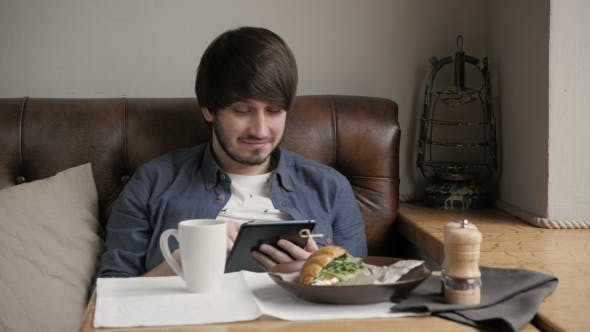 Cover Image for Hipster Man Using Digital Tablet  Eating Healthy Breakfast