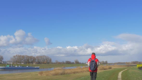 Tourist is Walking Away Along a River by Meadow