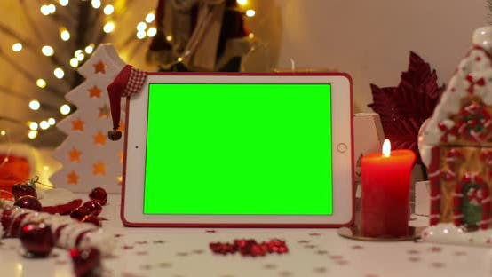 iPad Air with green screen on a background of Christmas tree and holiday lights. App promo, Zoom in