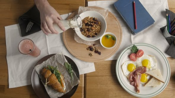 Thumbnail for Top View Of Healthy Breakfast In Cafe.Man Pouring Milk In Granola, English Breakfast: Fried Egg