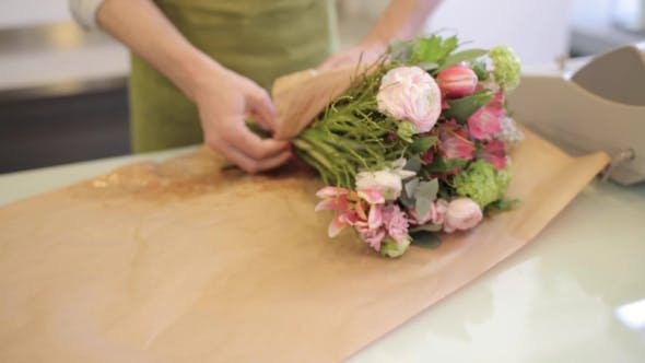 Thumbnail for Florist Wrapping Flowers In Paper At Flower Shop 12