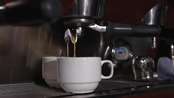 Thumbnail for Two White Cups Standing On The Grating Of Coffee Machine And Coffee Pouring Into Them