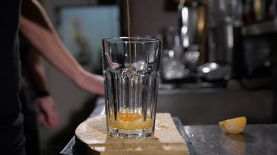Bartender Is Making Cocktail. Bartender Adds Honey Syrup In a Glass