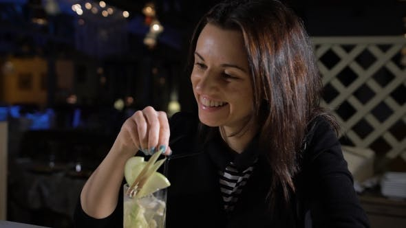 Thumbnail for The Girl In The Bar Drinking Cocktails And Laughs. Attractive Brunette In a Restaurant