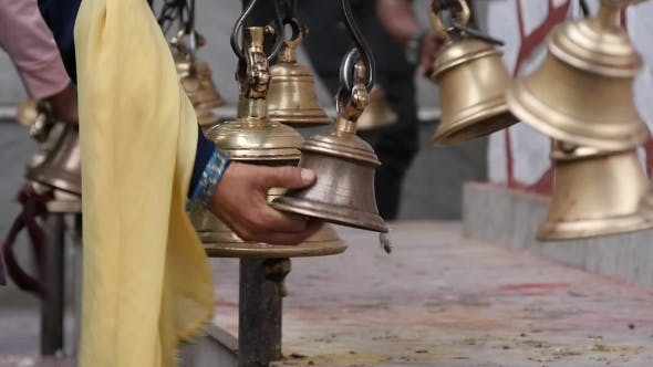 Woman's Hand Shaking a Bell