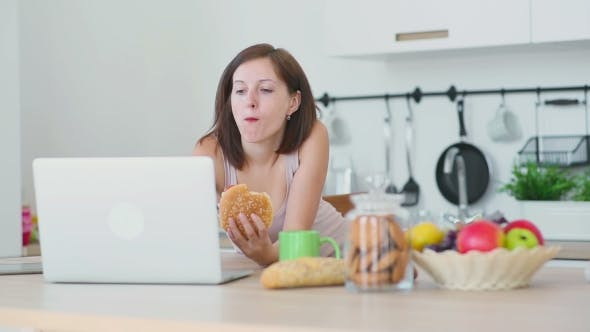Thumbnail for Woman Eats Hamburger And Works With Laptop