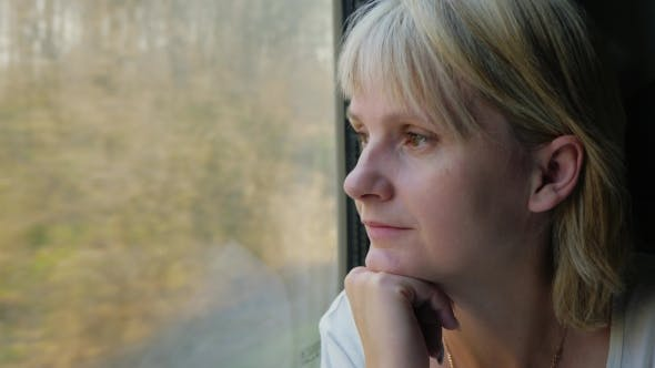 Thumbnail for Portrait Of a Young Pensive Woman Who Is Looking Out Of The Train Window