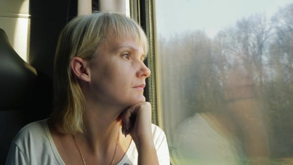 Thumbnail for A Woman Looks Out The Window Of The Train