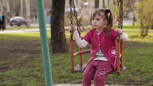 Sad Little Girl Swinging On a Swing