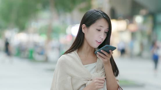 Thumbnail for Woman sending audio message on cellphone in city